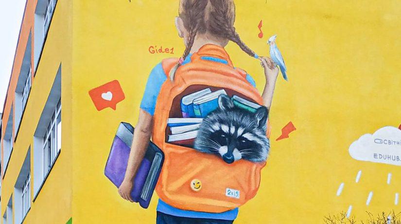 На Березняках появился яркий мурал со школьницей с енотом в рюкзаке