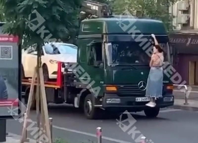 Не тільки коня, а й евакуатор зупинить. Жінка залізла на бампер вантажівки, захищаючи свою автівку (ВІДЕО)